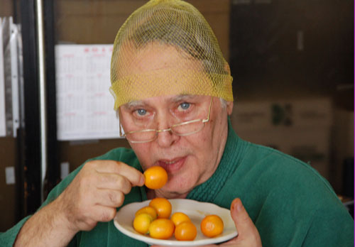 Mr. Goudas - Peter Spyros Goudas with hair net eating kumquats.